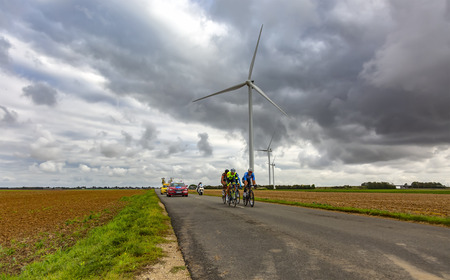 Le Gault-Saint-Denis, France - October 08, 2017: The breakaway riding on a road in the plain with windmills in a cloudy day during the Paris-Tours road-cycling race.