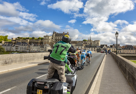 Amboise,France - October 8,2017: A photographer on a bike photographing the breakaway passing on the bridge in front of Amboise Castle during the Paris-Tours road cycling race. Redactioneel