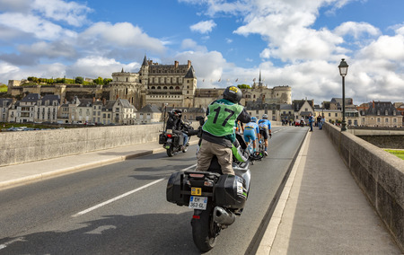 Amboise,France - October 8,2017: A photographer on a bike photographing the breakaway passing on the bridge in front of Amboise Castle during the Paris-Tours road cycling race.