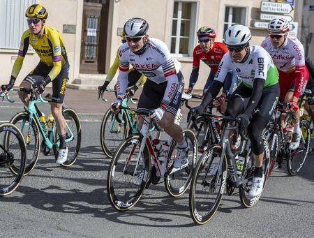 Chatillon-Coligny, France - March 10, 2019: Three cyclists (Andre Greipel of Arkea-Samsic Team, Lars Ytting Bak of Dimension Data Team, Mike Teunissen of Team Jumbo-Visma) riding in the peloton, in Chatillon-Coligny during the stage 3 of Paris-Nice 2019. Editorial