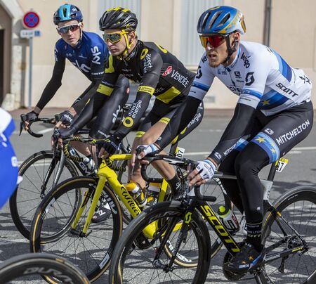 Chatillon-Coligny, France - March 10, 2019: Three cyclists (Matteo Trent of Mitchelton-Scott Team, Anthony Turgis of Direct Energy Team, Tao Geoghegan Hart of Sky Team) riding in the peloton, in Chatillon-Coligny during the stage 3 of Paris-Nice 2019.