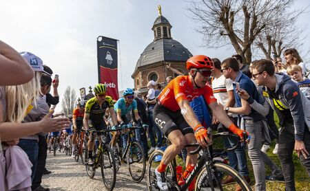 Muur van Geraardsbergen, Belgium - April 7, 2019 : The peloton is passing through a crowd of excited psectators on the top of the famous Muur van Geraardsbergen during Tour of Flanders 2019. Editoriali