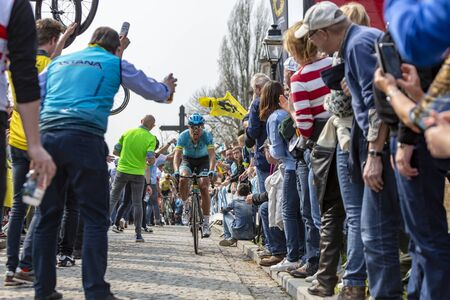 Muur van Geraardsbergen, Belgium - April 7, 2019 : The Danish cyclist Magnus Cort Nielsen of Team Astana is passing through a crowd of excited psectators on the top of the famous Muur van Geraardsbergen during Tour of Flanders 2019.