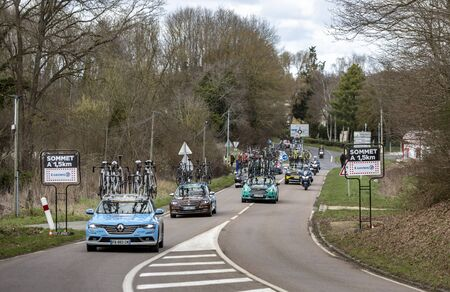Les Granges-le-Roi, France - March 11, 2019: Row of teams technical cars driving on Cote des Granges-le-Roi during the stage 2 of Paris-Nice 2019.