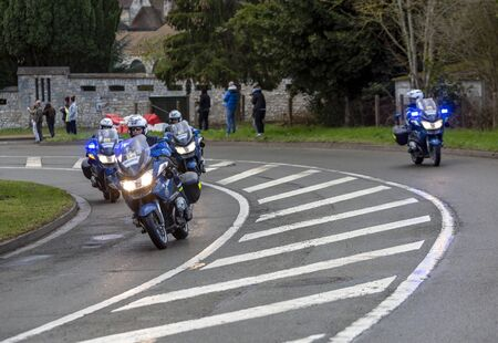Beulle, France - March 10, 2019: Group of police bikers driving, before the aparition of the peloton, on Cote de Beulle during the stage 1 of Paris-Nice 2019.