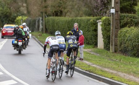 Beulle, France - March 10, 2019: Rear view of the breakaway (Damien Gaudin of Direct Energie ,Evaldas Siskevicius of Delko-Marseille Provence, Warren Barguil of Arkea-Samsic) riding in front of the race on Cote de Beulle during the stage 1 of Paris-Nice 2