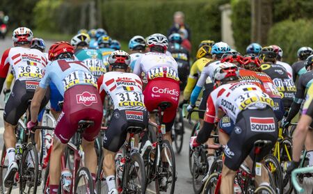 Beulle, France - March 10, 2019: Rear view of the peloton riding on Cote de Beulle during the stage 1 of Paris-Nice 2019. Publikacyjne