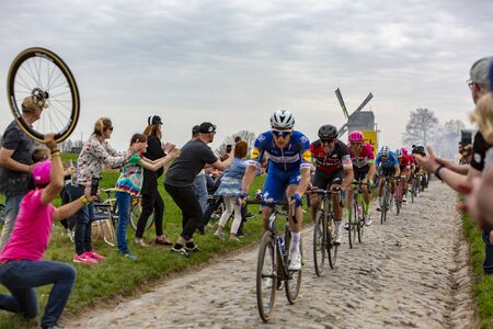Templeuve, France - April 08, 2018: The peloton riding on the cobblestone road in Templeuve in front of the traditional Vertain Windmill during Paris-Roubaix 2018. Publikacyjne