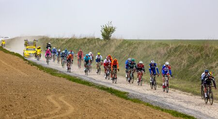 Viesly, France - April 14, 2019: The peloton riding on the dusty cobblestone road from Briastre to Viesly during Paris Roubaix 2019. Publikacyjne