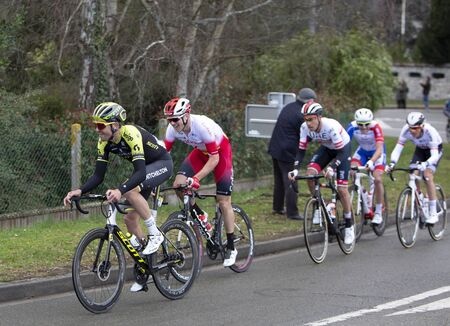 Beulle, France - March 10, 2019: Group of cyclists (Jack Bauer of Mitchelton-Scott, Bert Van Lerberghe of Team Cofidis, Fabio Aru of UAE Team Emirates) riding on Cote de Beulle during the stage 1 of Paris-Nice 2019.