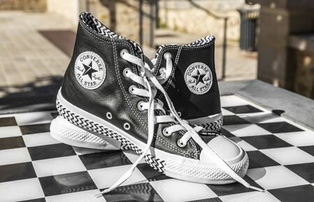 Chartres, France - Spetember 2, 2019: Image of a pair of All Star Converse sneakers on an urban black and white chess table