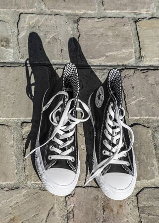 Chartres, France - Spetember 2, 2019: Aerial view image of a pair of All Star Converse sneakers on a cobblestone street.
