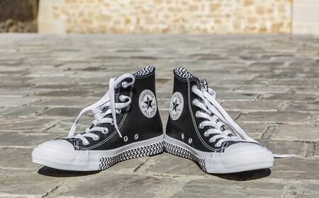 Chartres, France - Spetember 2, 2019: Image of a pair of All Star Converse sneakers on a cobblestone street.