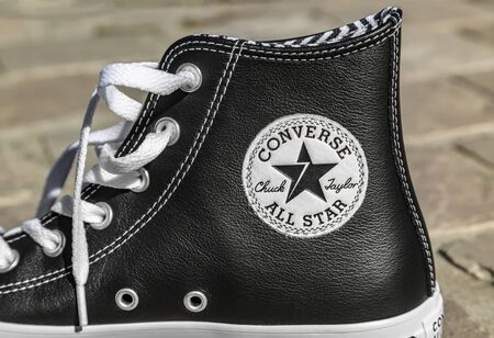 Chartres, France - Spetember 2, 2019: Close-up of the upper part of an All Star Converse sneaker featuring the logo of the company in a cobblestone street in the city