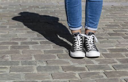 Chartres, France - Spetember 2, 2019: Image of the lower part of teenager's legs in jeans and All Star Converse sneakers in a cobblestone street.