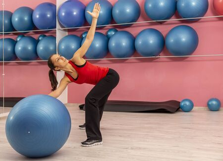 Portrait of a young woman doing exercises with a fitness ball in a gym 스톡 콘텐츠