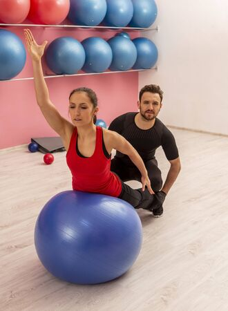 Young woman helped by her coach is doing exercises with a fitness ball in a gym.