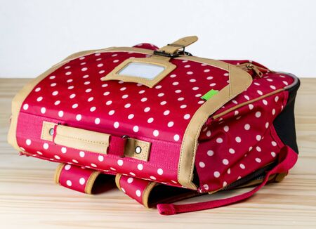 Fancy red schoolbag with white dots is on a wooden table next to a white wall