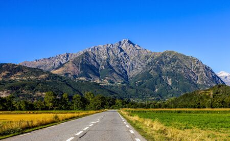 Image of a road going direct to big mountains. It is The Napoleon Road in France leading to Ecrins Massif.