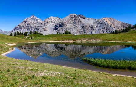 Le Rois Mages (Baltazar 3153m, Melchior 2948 m, Gaspard 2808 m , Quatre Soeurs 2587 m) and their reflection in the lake Chavillon on Etroite Valley- Hautes-Alpes. Banque d'images