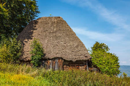 """Landscape in an isolated mountainous rural area in Apuseni Mountains in Transylvania Romania. The place is known as """"Motilor country"""". The house is made exclusively by wood with any pieces of iron."""