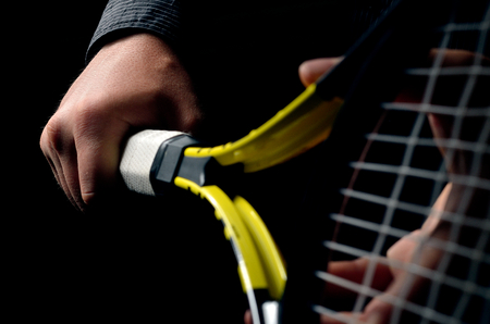 Hand on grip and swinging a tennis racket. Isolated on black background. Stock Photo