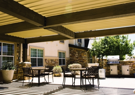 porches: Covered hotel patio with tables and barbeque in summer light