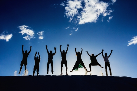 against the sun: Black silhouettes of seven enthusiast people jumping on sand  Blue sky behind  Stock Photo