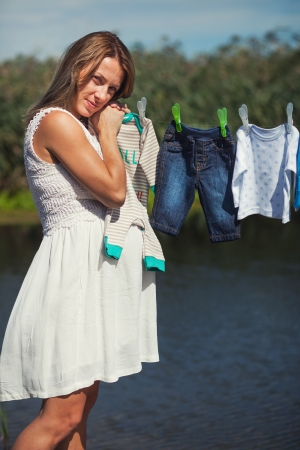 beatitude: Serenity of a pregnant lady next to laundry line with baby clothes