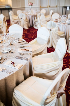 Indoor elegant wedding setting with round tables and chairs with beige cover Stock Photo - 24609519