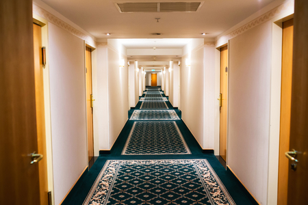 Perspective of a hotel hallway with room doors and warm light