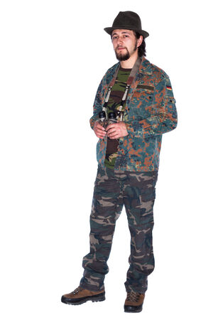 animal watching: Young hunter wearing camouflage uniform holding binocular in his hands is prepared for animal watching