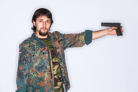 finger on trigger: Young suicidal soldier with camouflage jacket is pointing a gun to his head holding his finger on the trigger - isolated on white