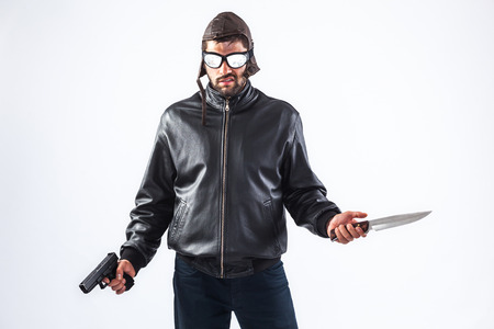 Dangerous and violent criminal wearing cap and glasses is holding a gun and a knife in his hands - isolated on white photo