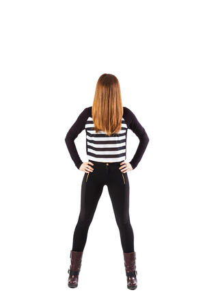 enigmatic: In piedi donna enigmatica con il viso coperto con i capelli tiene le mani sui fianchi - isolati su bianco Archivio Fotografico