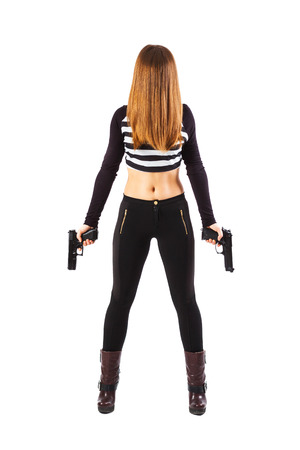 instigator: Enigmatic and instigant female spy with hair over face is holding two guns in her hands pointed downwards - isolated on white