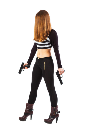holding hands while walking: Threatening, mysterious and sexy woman with hair over face is walking while holding two guns in her hands - isolated on white Stock Photo
