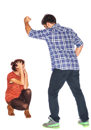 assault: Frightened and crying woman next to angry husband holding his fist upwards - domestic violence - isolated on white