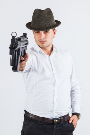 assasin: Young handsome man holding a gun with one hand focused on his target - isolated on white Stock Photo