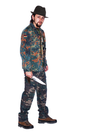 A young man wearing camouflage clothes is holding a dagger in his right hand - isolated on white photo