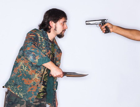 A young man wearing camouflage clothes and holding a dagger in his hand is threatened with a gun pointed to his head by another unknown man - isolated on white