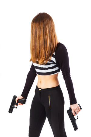 instigator: Mysterious sexy female spy holding two guns in hands is walking - isolated on white