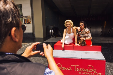 Los Angeles, CA, USA - may 2013: Tourist taking a photo with the life size wax figure of Marilyn Monroe which is displayed on the sidewalk of  Boulevard outside of Madame Tussauds Museum Editorial