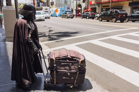 fictional character: Los Angeles, CA, USA - may 2013: Person dressed as fictional character Darth Vader is crossing the street carrying luggage Editorial
