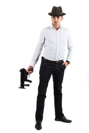Young handsome man, member of italian mafia, is holding a weapon in his hand - isolated on white photo
