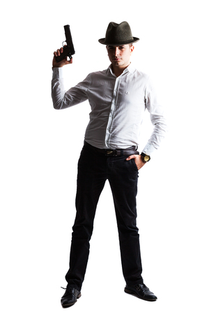 Shadow and light on a criminal holding gun - isolated on white photo