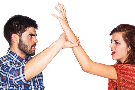 Aggressive man hurting a woman during a fight - isolated on white photo