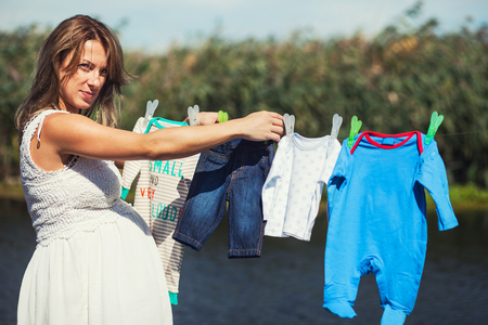 Young and beautiful pregnant woman is hanging the clothes of her baby boy on a string in the backyard photo