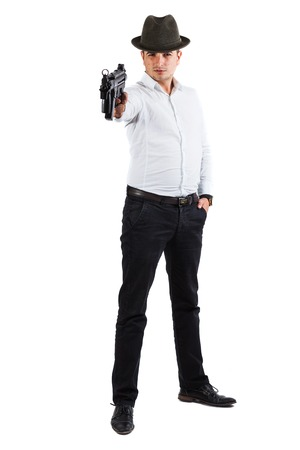 Young handsome man is using a gun to threaten - isolated on white photo