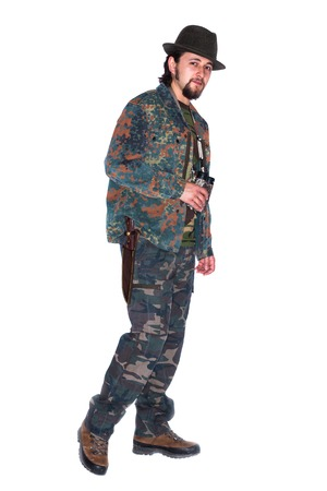 categorical: Standing young bearded hunter equipped with dagger and binocular wearing camouflage uniform